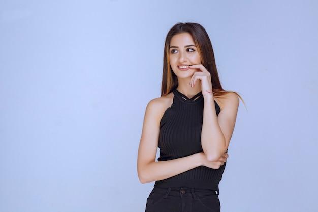 Woman in black shirt smiling.
