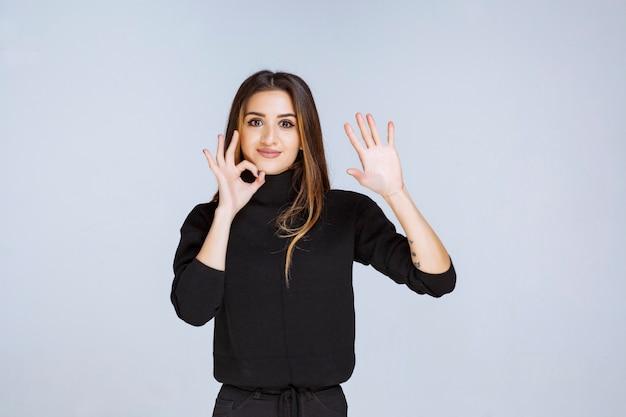 Donna in camicia nera che si ferma e impedisce qualcosa.