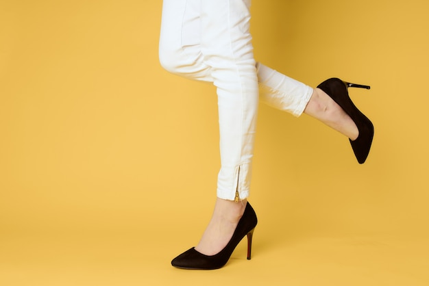 Woman in black shoes legs clipped lit yellow fashion shopping.