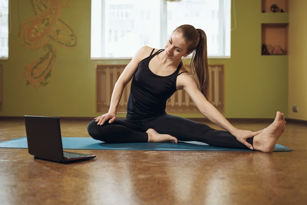 Woman in black sportswear doing yoga sitting on a mat performing online flexibility exercises looking into a laptop