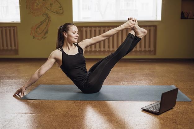 Woman in black sportswear is engaged in yoga