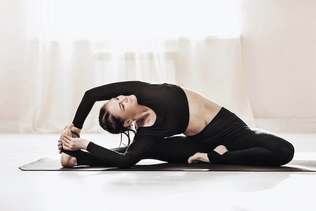 Woman in black sportswear practicing yoga at home sitting on a gymnastic mat performs the exercise parivrtta janu shirshasana