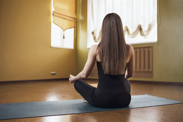 Woman in black sportswear practicing yoga is engaged in meditation in the lotus position on a gymnastic mat in the studio