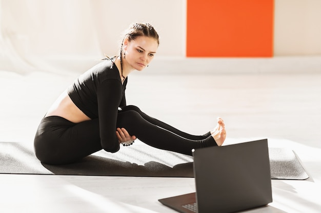 Woman in black sportswear sitting on a gymnastic mat is looking closely at the laptop screen online sports concept