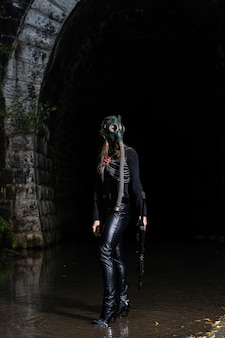 A woman in a black suit and gas mask with a machine gun in her hands