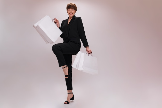 Woman in black suit happily posing with bags after shopping. short-haired lady in dark jacket and pants dances and moves on white backdrop