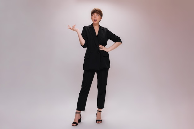 Woman in black suit posing with misunderstanding on white background. full-lenght portrait of attractive lady in classic style outfit on isolated