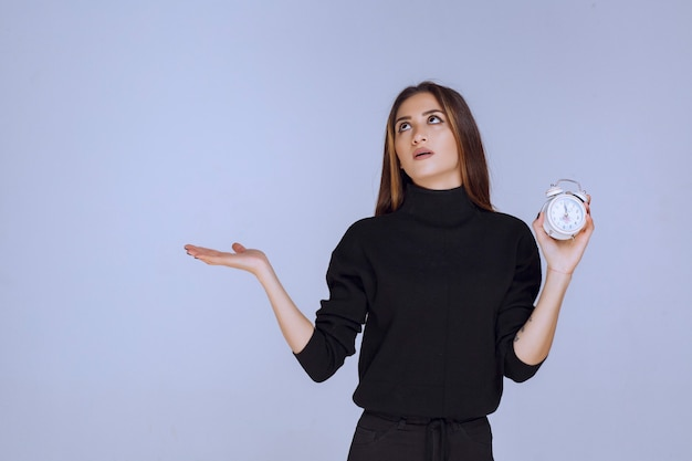 Woman in black sweater holding the alarm clock and promoting it.