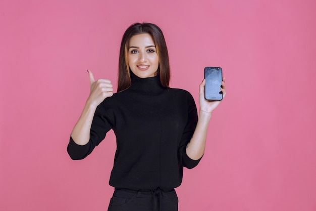 Woman in black sweater holding a smartphone and making thumb up.