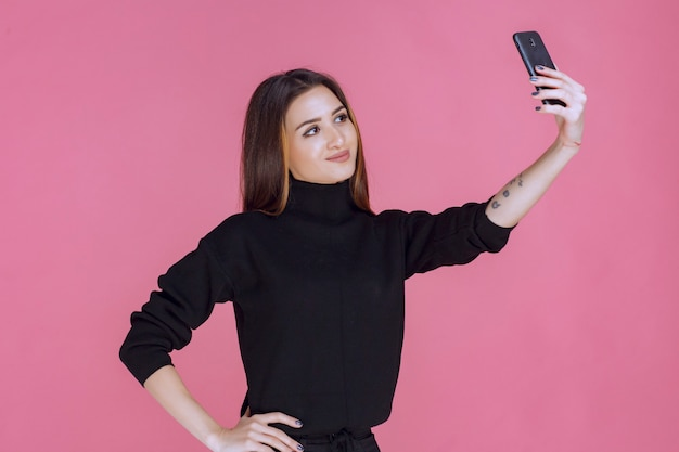 Woman in black sweater holding a smartphone and taking her selfie.