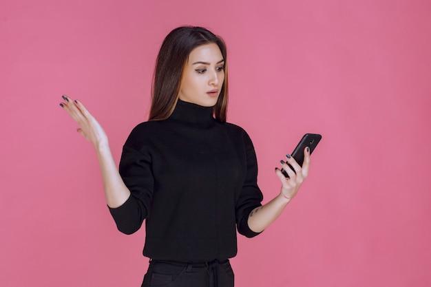 Donna in maglione nero che tiene uno smartphone e mandare sms o controllare i social media.