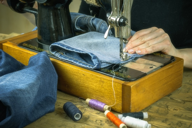 The woman in the black sweater works on old sewing machine.