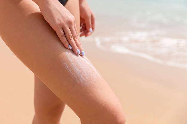 Woman in a black swimsuit is applying sun cream with her fingers on her leg at the sea background.