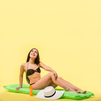 Woman in black swimsuit sitting on water mattress and smiling