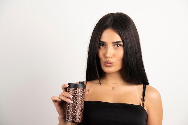 La donna nella parte superiore nera che tiene tazza di caffè su fondo beige. foto di alta qualità
