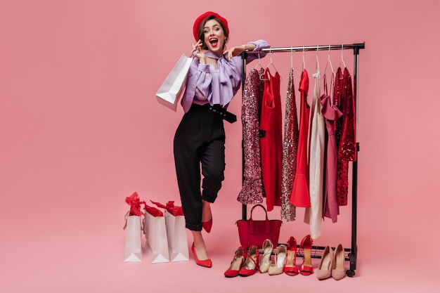 Woman in black trousers and purple blouse laughs, leaning on stand with elegant clothes on pink background.