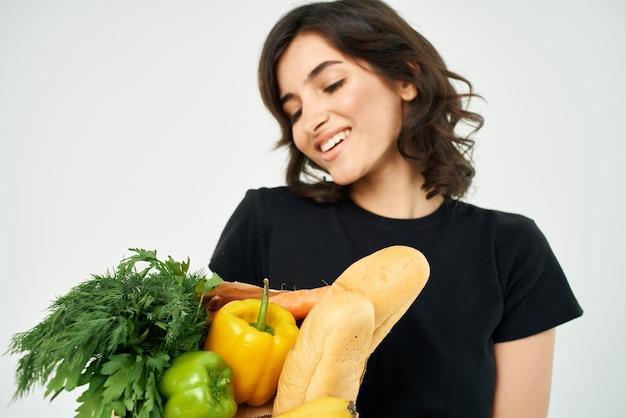Woman in black tshirt package with groceries healthy food homework