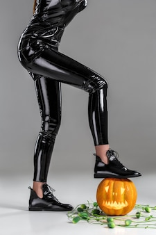 Woman in black vinyl jumpsuit and flat ankle boots leaning on carved pumpkin lantern