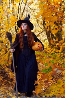 A woman in a black witch costume and a pointed hat with a broom and a pumpkin in a park on halloween