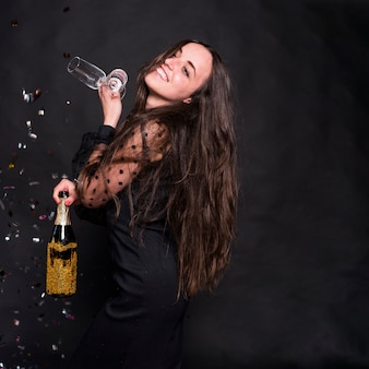 Woman in black with champagne bottle and glasses
