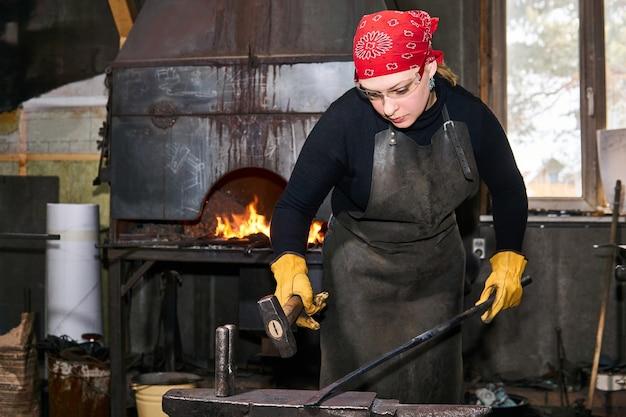女性の鍛冶屋の金属アーティストは、伝統的なワークショップでアンビルにハンマーで溶銑ワークピースを鍛造します