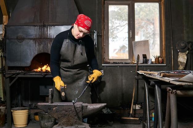 女性の鍛冶屋の金属アーティストは、伝統的なワークショップでアンビルにハンマーで形作られた金属ブランクを鍛造します