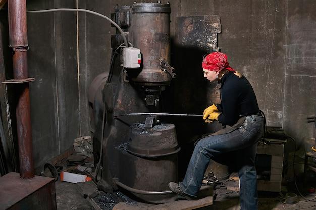 Женщина-кузнец обрабатывает горячую деталь силовым молотком в мастерской