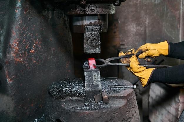 女性の鍛冶屋は、ワークショップでパワーハンマーで赤熱したワークピースを処理します