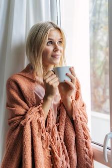 Donna in coperta a casa durante la pandemia seduto accanto alla finestra e bere un caffè