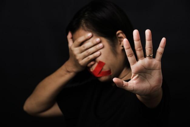 빨간 접착 테이프로 입을 눈가리개로 감싸고 폭력을 남용하지 않는 손 표시를 보여주는 여성