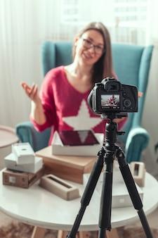 Женщина-блогер снимает дома видео распаковки гаджетов