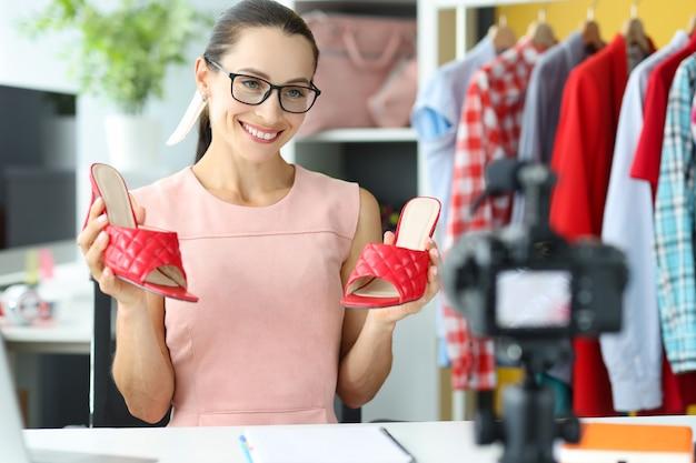 여성 블로거는 빨간 샌들 온라인 상점 및 제품 시연 개념에 대한 비디오 검토