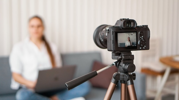 Woman blogger recording video indoors, selective focus on camera display. space for text