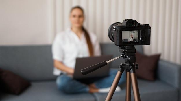 Женщина-блоггер, запись видео в помещении, селективный фокус на дисплее камеры. место для текста