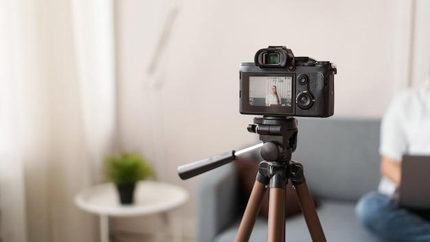 屋内でビデオを録画する女性ブロガー、カメラディスプレイに選択的に焦点を合わせます。テキスト用のスペース