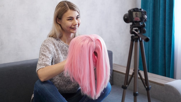 Woman blogger records video. she talks about haircuts and shows a pink wig. stylist and fashion consultant recording the lecture Premium Photo