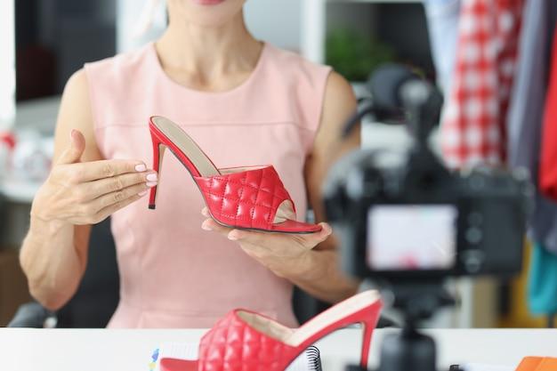 카메라 근접 촬영 앞에서 빨간 신발을 보여주는 여성 블로거. 인터넷 블로깅 개념에 대한 프리랜서 수입