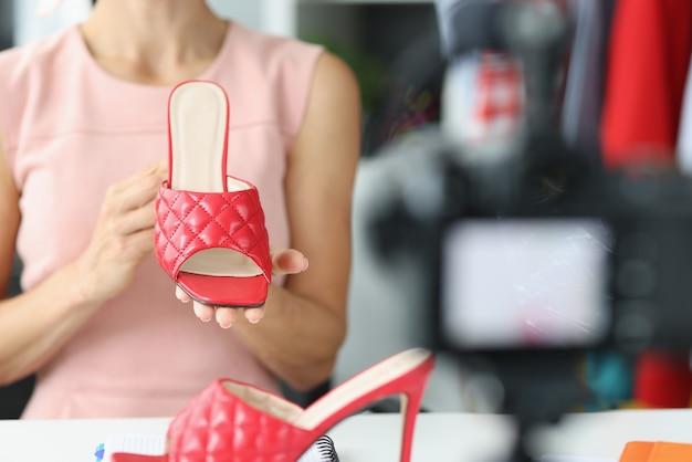Женщина-блогер демонстрирует новые красные босоножки из летней коллекции. обзор обуви от