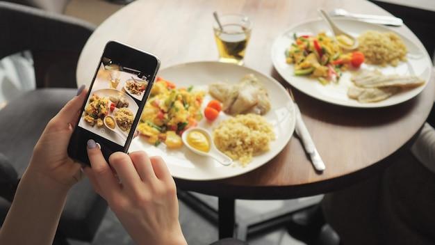 女性ブロガーが携帯電話を使ってカフェで食事の写真を撮る。電話スクリーンのクローズアップと手。