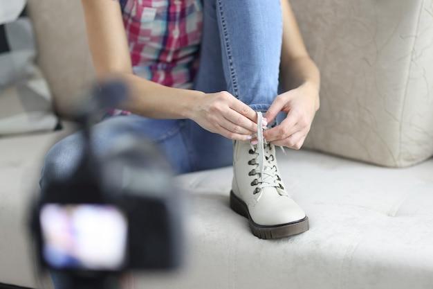 그녀의 신발에 신발 끈을 묶고 근접 촬영을 촬영하는 여성 블로거
