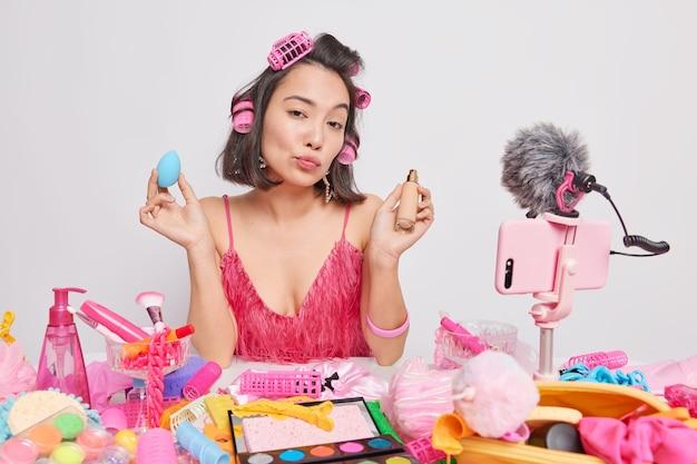 여성 블로거는 비디오 블로그를 위해 새로운 콘텐츠를 작업하고 있으며 얼굴에 기초를 올바르게 적용하는 방법에 대한 조언을 제공하여 새로운 화장품 제품이 지저분한 테이블에 놓여 있는 헤어스타일 테스트를 만듭니다.