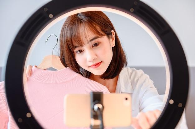 Женщина ведет блог в интернете и транслирует в прямом эфире. азиатский предприниматель использует социальные сети для ведения бизнеса дома. новый нормальный образ жизни и социальное дистанцирование.
