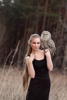 Женщина блондинка осенью в шубе с совой в наличии первый снег. красивая девушка с длинными волосами в природе, держа сову. романтичный, нежный взгляд девушки