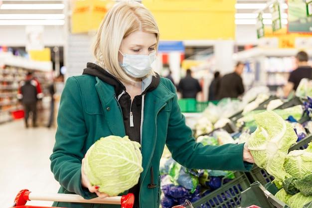 医療マスクで金髪の女性はスーパーで野菜を選択します。パンデミックにおける自己隔離。