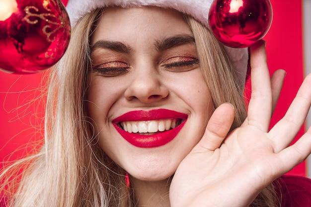 赤い唇の魅力的な化粧品のクリスマスのクローズアップと金髪の女性