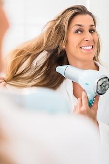 Женщина сушит волосы перед зеркалом