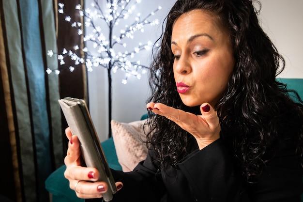クリスマスに携帯電話にキスを吹く女性