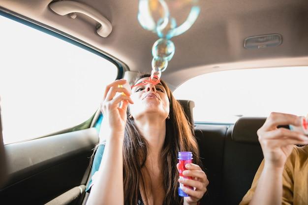 Woman blowing bubbles in car