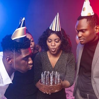 Donna che soffia candele sulla sua torta di buon compleanno