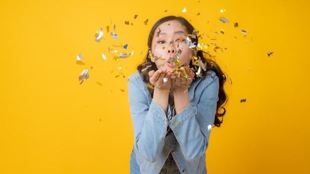 Женщина дует золотую бумагу конфетти